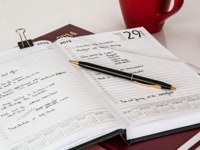un agenda est ouvert, un stylo posé dessus.